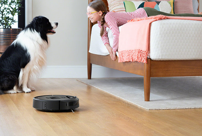 iRobot roomba with a girl in a bedroom